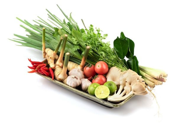 Tom yum zawiera chili, szalotkę, trawę cytrynową, liście limonki kaffir, cytrynę, galangal, kolendrę, cebulę i więcej na białym tle.