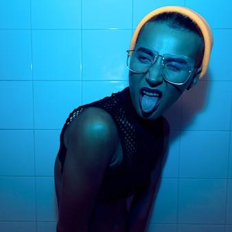 Tomboy agressive model w modnych okularach i modnym dodatku beanie cap i choker. neonowy styl imprezowy