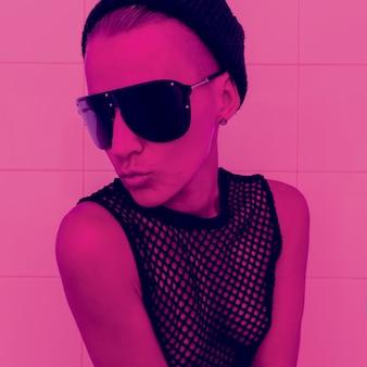 Tomboy girll in fashion dodatek beanie czapka i okulary przeciwsłoneczne. klubowa impreza glamour neon light