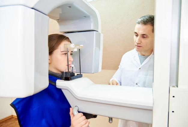 Tomografia stomatologiczna. dziewczyna-pacjent stoi w tomografie, lekarz w pobliżu panelu sterowania