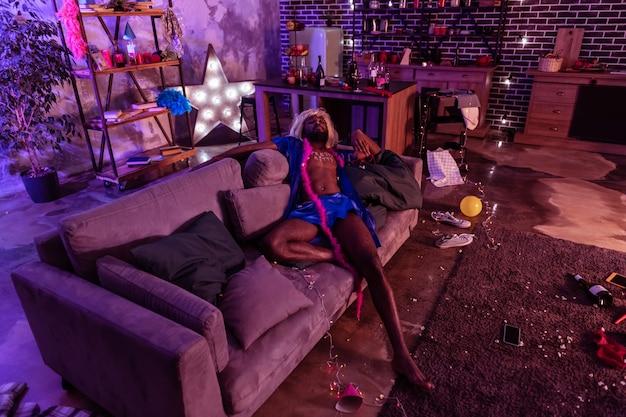 Ton alkoholu. dopasuj mężczyznę w kobiecym wizerunku tarzając się na poplamionej kanapie i ubrany w jedwabną piżamę kobiecą