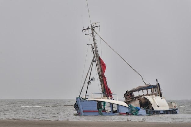Tonący opuszczony statek nad brzegiem morza pod czystym niebem