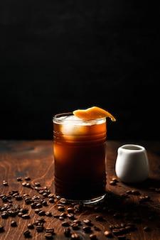 Tonik espresso z sokiem pomarańczowym w szklance typu highball z kulkami lodu przyozdobionym skórką pomarańczową, białą puszką i ziarnami kawy dookoła.