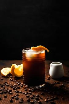 Tonik espresso z sokiem pomarańczowym w szklance typu highball z kulkami lodu przyozdobionym skórką pomarańczową, białą puszką, kawałkami pomarańczy i ziarnami kawy dookoła.