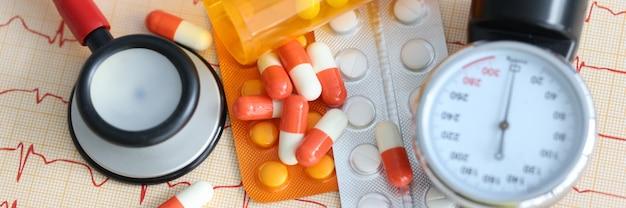 Tonometr i blister z tabletkami leżącymi na elektrokardiogramie diagnostyka i leczenie tętnic