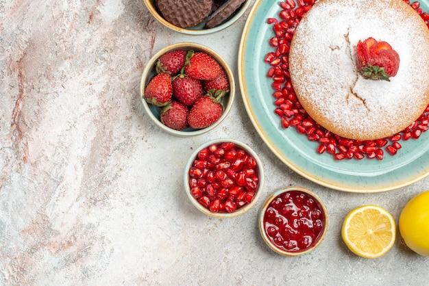 Top close-up view ciasta apetyczny placek z truskawek i granatu cytryna miski jagodowe ciasteczka na stole