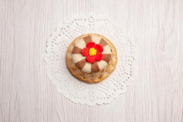 Top close-up view cupcake apetyczne ciastko na koronkowej serwetce na białym stole