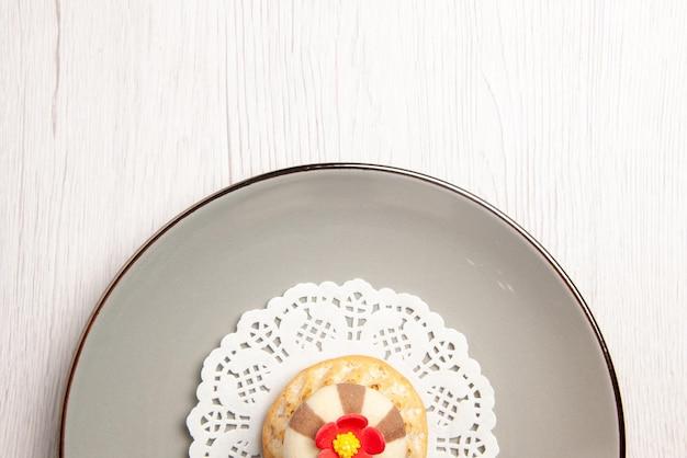 Top close-up view cupcake plate z apetyczną babeczką na białej koronkowej serwetce na stole