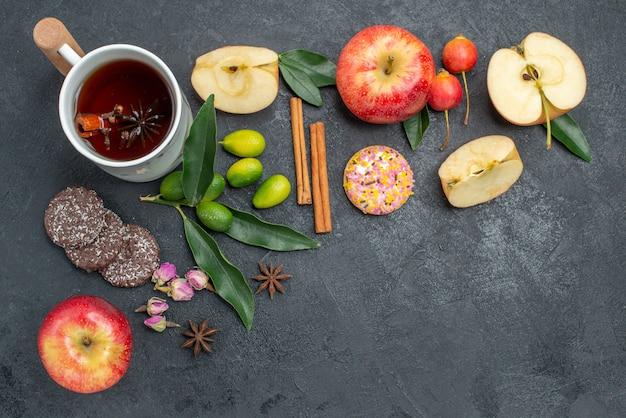 Top close-up view filiżanka herbaty filiżanka herbaty ziołowej laski cynamonu jabłka ciasteczka owoce cytrusowe