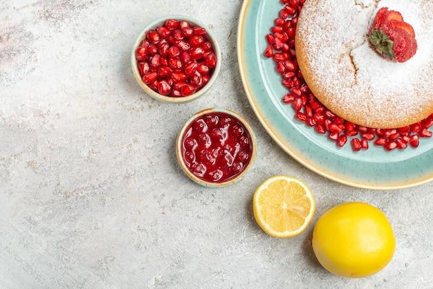 Top close-up view tort z jagodami apetyczny tort z jagodami granat ciasteczka czekoladowe cytryna