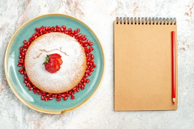 Top close-up view truskawki ciasto krem notatnik czerwony ołówek obok talerza ciasta z truskawkami i granatem na stole