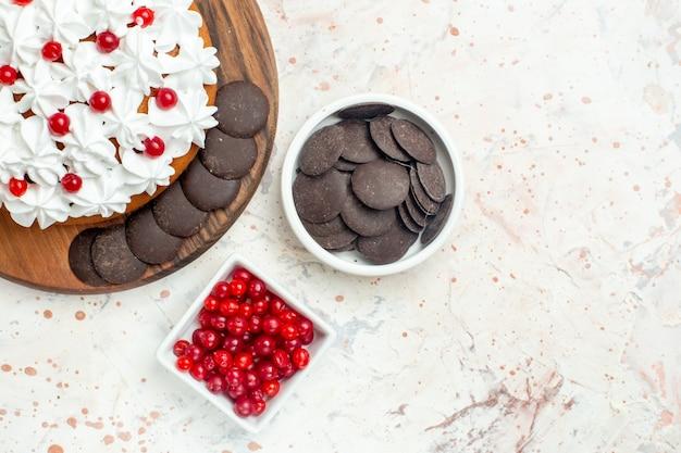 Top half view ciasto z kremem cukierniczym i czekoladą na desce do krojenia miski z jagodami i czekoladą