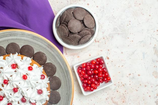 Top half view ciasto z kremem cukierniczym i czekoladą na talerzu fioletowe miseczki szalowe z czekoladą i jagodami