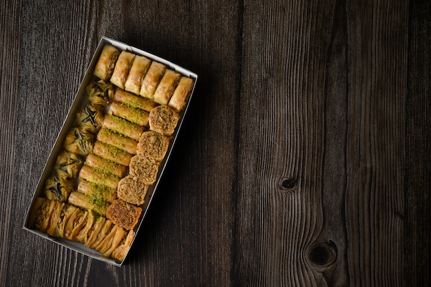 Top of view turecka baklava słodkie ciasto z pudełkiem na białym tle drewniane