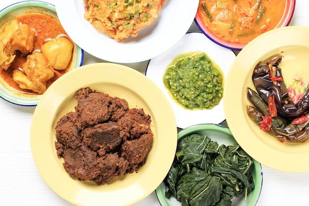Top view rendang lub randang to najsmaczniejsze jedzenie na świecie. wykonane z gulaszu wołowego i mleka kokosowego z różnymi ziołami i sosem. zazwyczaj jedzenie z plemienia minang, west sumatera, indonezja