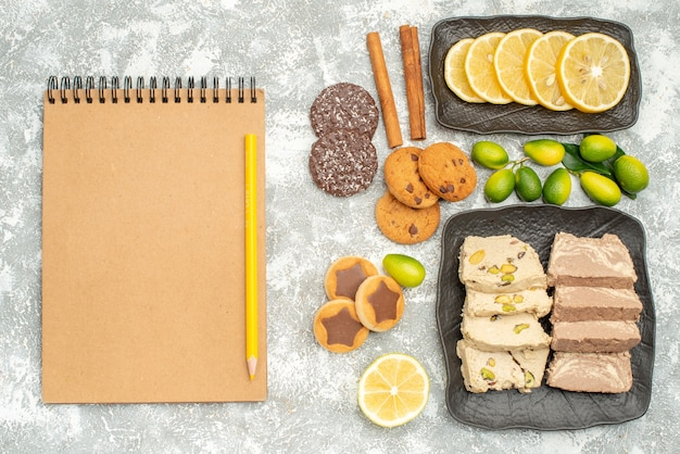 Top zbliżenie słodycze ciasteczka nasiona słonecznika chałwa owoce cytrusowe cynamon ołówek notatnik