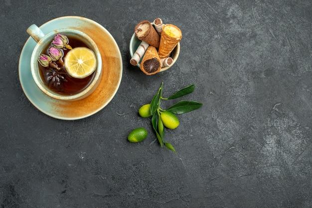 Top zbliżenie słodycze gofry w misce kubek ziołowej herbaty owoców cytrusowych