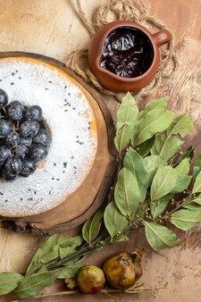Top zbliżenie widok ciasto ciasto z winogronami na pokładzie liści sosu czekoladowego