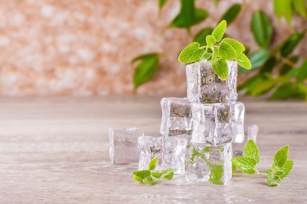 Topienie kostek lodu i liści mięty na drewnianym stole