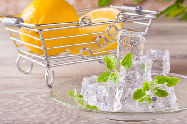 Topienie kostek lodu i liści mięty na spodku i plasterki cytryny w koszu na drewnianym stole