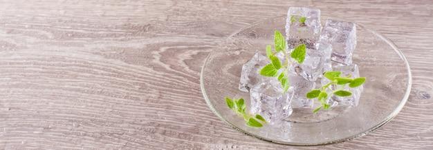 Topienie kostek lodu i liści mięty na spodku na drewnianym stole