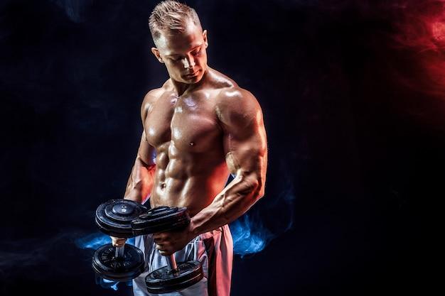 Topless mężczyzna ćwiczy biceps z dumbbells wewnątrz