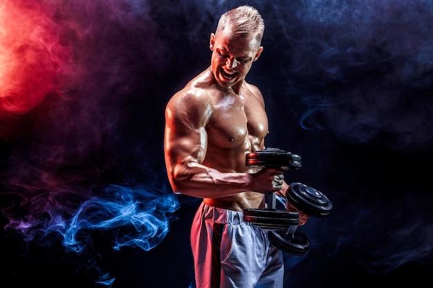 Topless mężczyzna ćwiczy bicepsy z hantlami pozowanie w studio pełne