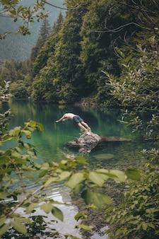 Topless mężczyzna w czarnych szortach ma zamiar nurkować na wodzie w pobliżu drzew