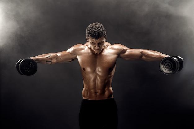 Topless muskularny mężczyzna robi ćwiczenia z hantlami