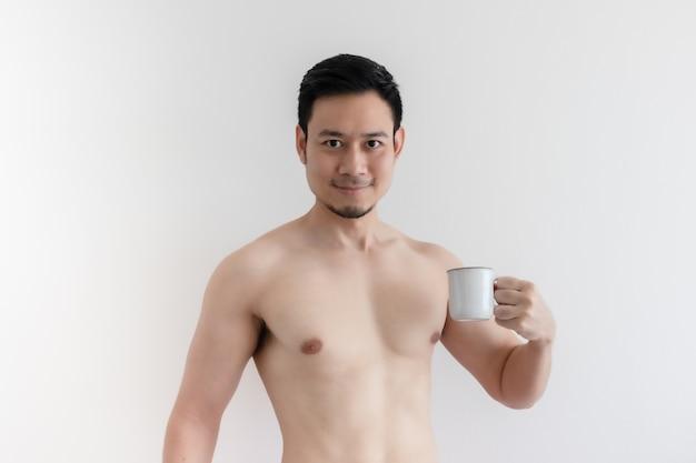 Topless zdrowy azjatycki mężczyzna pije zdrową kawę na białym tle