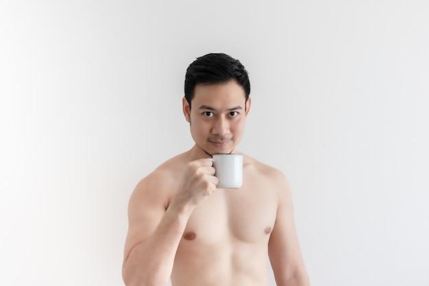 Topless zdrowy azjatycki mężczyzna pije zdrową kawę na na białym tle.