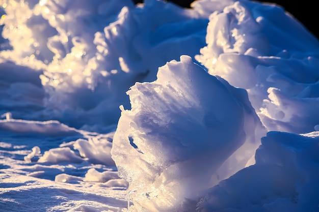Topniejący śnieg i lód z bliska w wieczornym słońcu w okresie zimowym