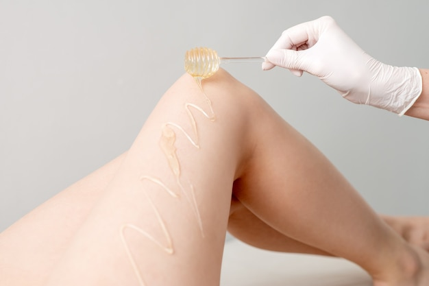 Topór woskowy spływa po patyczku miodu na nodze podczas koncepcji depilacji i depilacji trzymanej za rękę