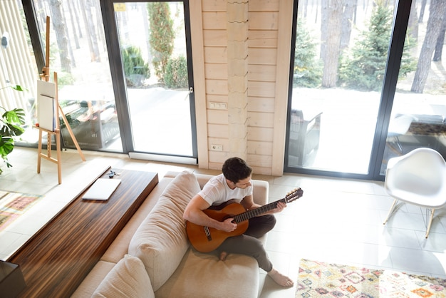 Topview gry na gitarze na kanapie