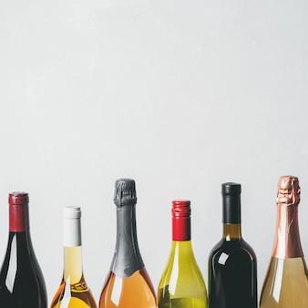 Topy z różnych rodzajów nowych butelek szampana, białego, czerwonego wina na jasnym tle