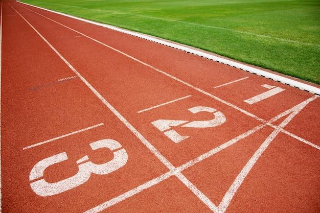 Tor dla sportowców lub bieżnia z trzema numerami pasów i trawnikiem