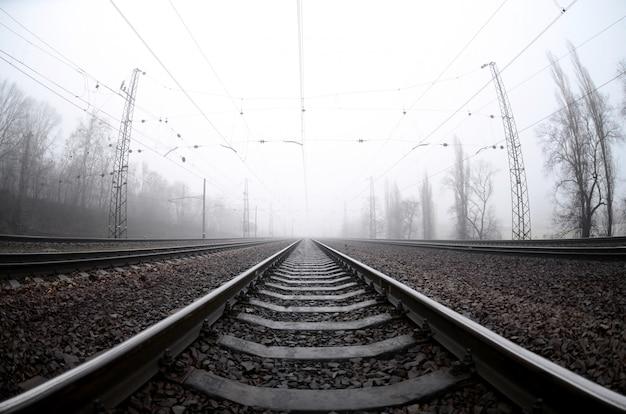 Tor kolejowy w mglisty poranek. wiele poręczy i podkładów wchodzi na mglisty horyzont