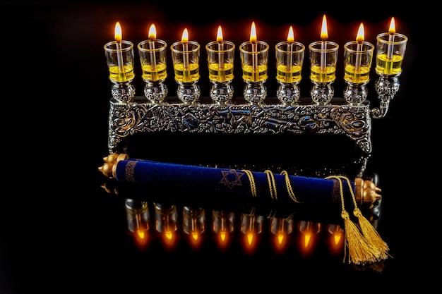 Tora i menora z płonącymi świecami oliwnymi z odbiciem.