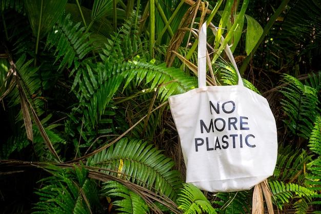 Torba ekologiczna bez więcej plastiku pośrodku zielonych świeżych tropikalnych liści