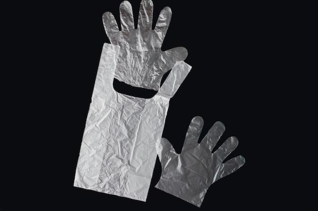 Torba foliowa z uchwytami, rękawiczkami, na czarnym tle. zużyty worek foliowy do recyklingu. koncepcja - ekologia, zanieczyszczenie planety plastikowym celofanem polietylenowym.