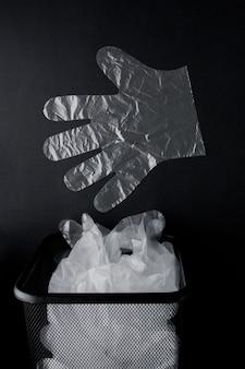 Torba foliowa z uchwytami, rękawiczki w koszu na czarnej powierzchni. zużyty worek foliowy do recyklingu. pojęcie ekologii, zanieczyszczenie planety plastikowym celofanem z polietylenu.
