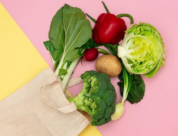 Torba i warzywa na różowym i żółtym tle