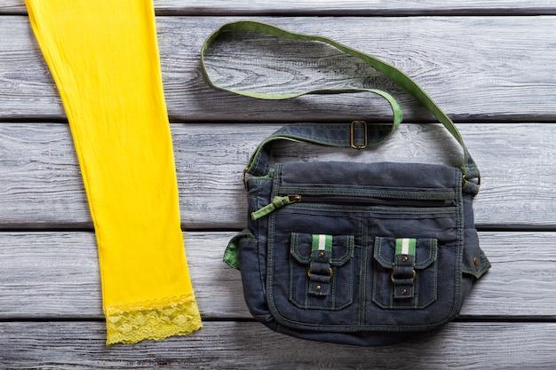 Torba jeansowa w kolorze granatowym. torebka na szarym drewnianym tle. swobodna torebka dziewczęca na wystawie. praktyczny i prosty.