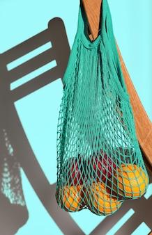 Torba materiałowa z owocami z tyłu krzesła, materiał wielokrotnego użytku na produkty naturalne. świadoma koncepcja konsumpcji bez odpadów z tworzyw sztucznych. zbliżenie, światło słoneczne, niebieska ściana