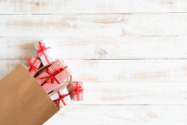 Torba na zakupy i prezenta pudełko na drewnianym białym tle. koncepcja dzień boxing.