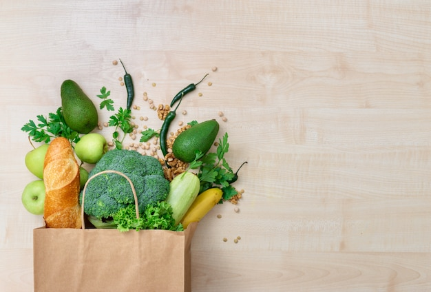 Torba na zakupy spożywcze ze zdrową żywnością na drewnianym widoku z góry