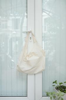 Torba na zakupy wielokrotnego użytku wisząca na wieszaku na drzwi wejściowe, recykling i koncepcja zrównoważonych zakupów