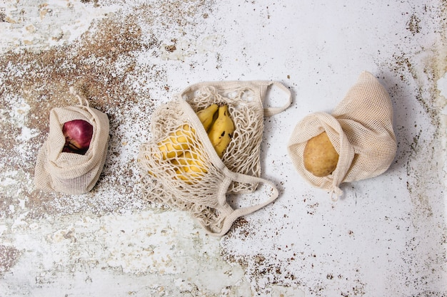 Torba na zakupy wielokrotnego użytku z bananami i torebkami z tkaniny roślinnej z ziemniakami i cebulą na stole