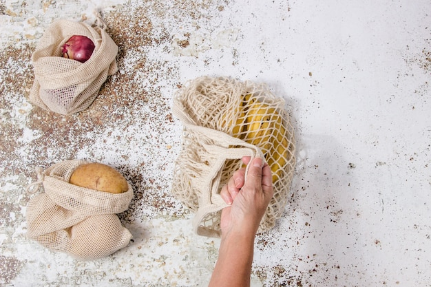 Torba na zakupy wielokrotnego użytku z bananami i torebkami z tkaniny roślinnej z ziemniakami i cebulą w stole i ktoś bierze jedną z tych toreb