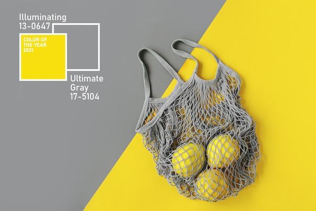 Torba na zakupy wielokrotnego użytku z cytrynami. kolory roku 2021 ultimate grey i illuminating. paleta trendów kolorystycznych. stylowe tło